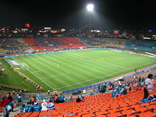 An all-seated roofless stadium with a football pitch.