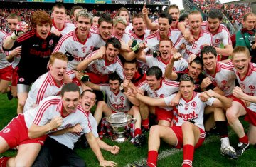 The Tyrone minor squad gather around the Tom Markham Cup to celebrate their victory over Cork in the All-Ireland minor football championship final at Croke Park yesterday. It was Tyrone's fifth success at this level this decade, indeed century, nay millennium. - (Photograph: Eric Luke)
