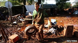 Resident of the flooded village of Devecser cleans up a yard covered in toxic sludge, 11 October 2010