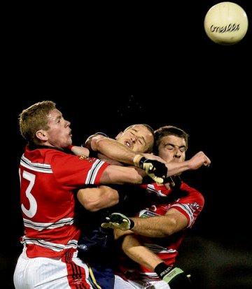 Australia's Daniel Cross is tackled by Andrew O'Sullivan and Andrew O'Brien of UCC/CIT during last night's match at Páirc Uí Rinn