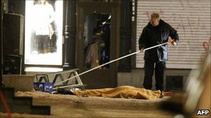 A police forensics officer examines the area around the man killed in Stockholm, 11 December