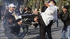 Rioters attack a policeman in Tunis