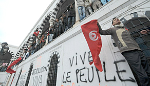 Protesters gather outside the Interior Ministry in Tunis yesterday to demand the removal of members of the ousted president's regime