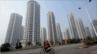 Chinese woman riding bicycle pass a group of newly-built properties