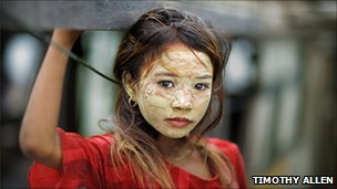 Bajau girl, her face covered in rice paint for sun protection