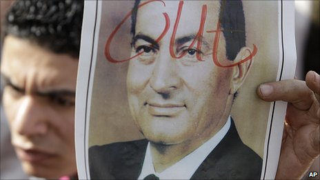 Protester holds photo of Hosni Mubarak with 'out' written across it