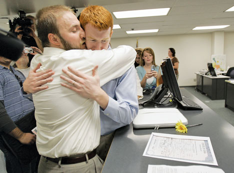 Sean Fritz, left, embraces his new husband Tim McQuillan after they received their marriage certificate Friday in Des Moines. The Ames couple was married a day after a judge threw out the state's ban on same-sex marriage.