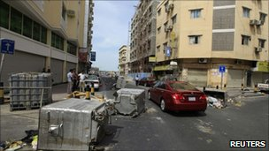 Cars pass garbage containers thrown onto the road in Manama 15 March