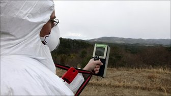 A scientist monitors radiation