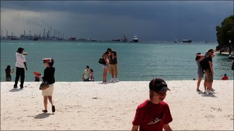Tourists on the beach at Sentosa Island in Singapore