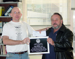 Tom hands Ron a check and Ron hands Tom a plaque