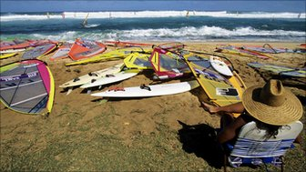 A wman in a straw hat on the beach amongst windsurfing equipment