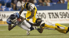 Toronto Argonauts slot back Brandon Rideau (left) is tackled Hamilton Tiger Cats defensive backs Jerome Dennis (centre) and Jason Shivers during first half CFL action in Toronto on Friday August 20, 2010.