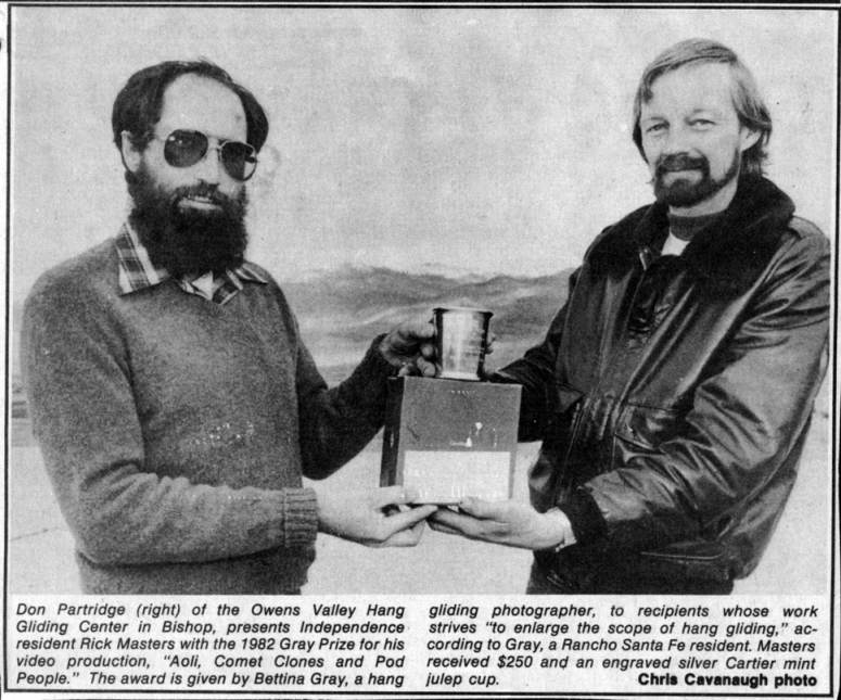 "Don Partridge (right) of the Owens Valley Hang Gliding Center in Bishop, presents Independence resident Rick Masters with the 1982 Gray Prize for his video production, ""Aoli, Comet Clones and Pod People."" The award is given by Bettina Gray, a hang gliding photographer, to recipients whose work strives ""to enlarge the scope of hang gliding,"" according to Gray, a Rancho Santa Fe resident.  Masters received $250 and an engraved Cartier mint julep cup.  Chris Cavenaugh photo"
