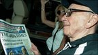 Rupert Murdoch reading a copy of The Times on the way back to his London home