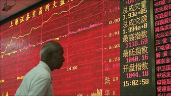 A Chinese investor looks at an electronic board displaying stock index