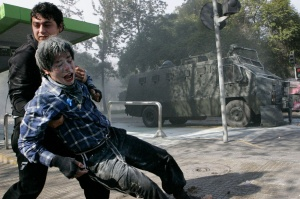 A demonstrator is helped after being affected by tear gas during a rally in Santiago July 14, 2011. Tens of thousands of students marched in Chile's capital on Thursday demanding changes in the public state education system. REUTERS/Victor Ruiz Caballero