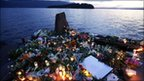 Flowers and candles commemorate the victims on the lake shore facing Utoeya island, Norway, 26 July