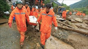 Rescue workers remove a body from a collapsed house in Chuncheon, about 100 km (60 miles) east of Seoul, July 27, 2011