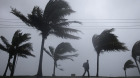 A man walks along a seaside park as Hurricane Irene passes to the east of Nassau on New Providence Island in the Bahamas, Thursday Aug. 25, 2011. Irene is pounding the Bahamas as a Category 3 hurricane.