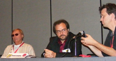 Adam West and Travis Langley (Papa Llama) listen as Comics Arts Conference co-founder Peter Coogan holds cell phone to microphone so Steve Englehart can address the crowd.