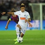 Neymar of Santos is challenged by Carles Puyol of Barcelona