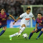 Neymar of Santos is challenged by Carles Puyol and Xavi of Barcelona