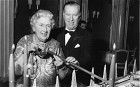 Agatha Christie and Peter Saunders cutting the cake, which weighed half a ton, at the tenth birthday party.
