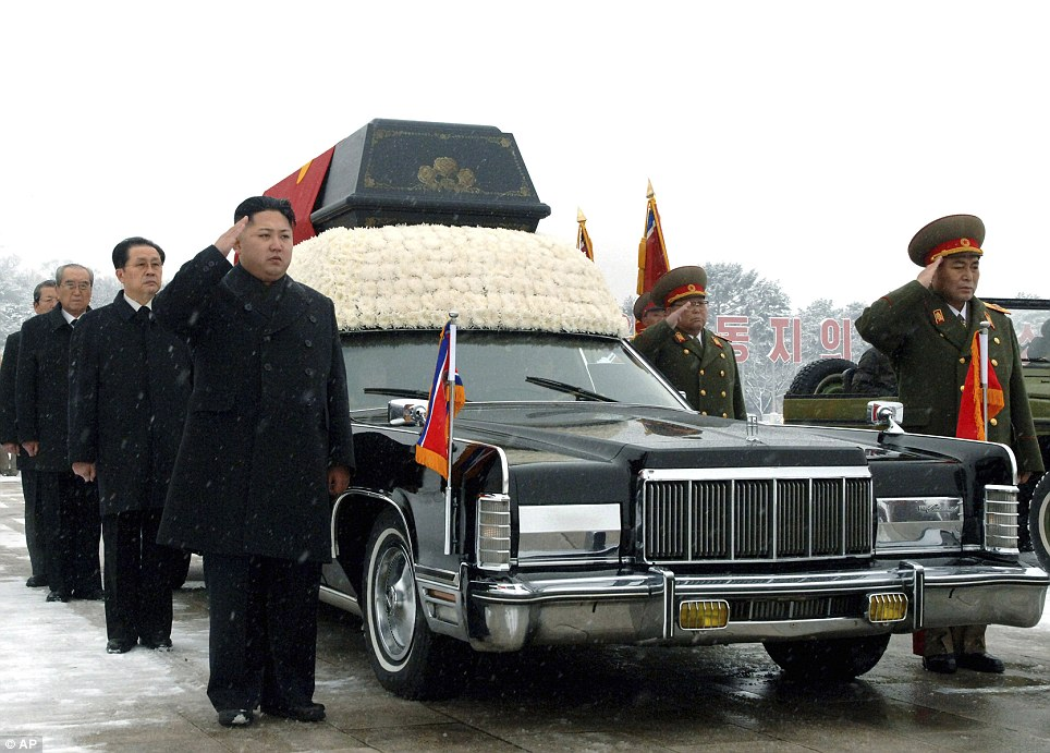 Passing the torch: North Korea's next leader, Kim Jong Un, front left, salutes beside the hearse carrying the body of his late father and North Korean leader Kim Jong Il during the funeral procession in Pyongyang, North Korea