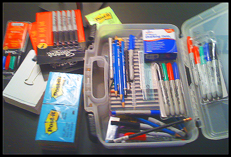 A bin of pens and supplies