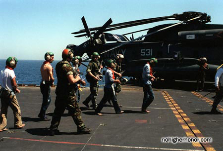 Aboard the amphibious assault ship USS <i>Guadalcanal</i> (LPH 7), detainees wearing helicopter headgear and hearing protection are escorted to waiting helicopters for transport to the <i>La Salle</i> during Operation Prime Chance, a part of the U.S. Navy's Operation Earnest Will.