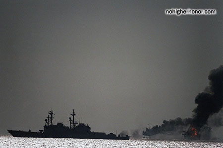 An Iranian command and control platform burns after being shelled by four US Navy destroyers. The shelling is a response to a recent Iranian missile attack on a reflagged Kuwaiti oil tanker.