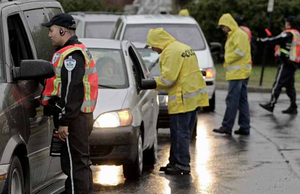 Police constable Emannuel Dupuis (left), joined officers from the Surete de Quebec (yellow rain jackets) pull over cars during a roadblocks on bridges in Montreal. Under current provincial and federal law, police can stop a vehicle to check the condition of the driver, including his or her sobriety. Police cannot request a breath sample unless they reasonably suspect that a driver is drunk.