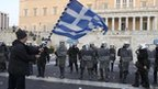A protester waves a Greek flag in front of police in Athens. Photo: February 2012