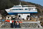 Then: People take pictures of a ship that was washed onto a building by the March 2011 magnitude 9.0 earthquake and tsunami in Otsuchi, Iwate prefecture, northeastern Japan April 17, 2011.