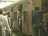 Mumbai commuters wait for a train the day after the bombing.