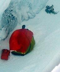 Японский альпинист, выглядывающий из палатки. Рядом, ниже по склону, лежит оранжевый спасательный пакет с припасами и рацией