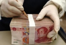 An employee packs yuan banknotes at a branch of Bank of China in Changzhi, Shanxi province February 24, 2010. REUTERS/Stringer