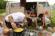 Kevin Eskew, Jackson, Ms., cooks eggs on a camping stove as his friends and travel buddies Zach Grey, left, Bret Slay (in van) and Noelle Suggs hang out nearby.  The four camped at last year's festival.