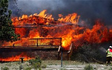 A firefighter works the scene of a home being consumed by flames in Estes Park, Colorado