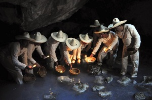 """Indigenous Zoque men carry baskets containing flowers and candles as offerings inside the cave of Villa Luz, during a ritual called """"The fishing of the blind Sardine"""" in Tapijualpa March 28, 2010. The ceremony is held during Holy week and is of pre-Hispanic origin when people asked deities for permission to fish inside the cave.     REUTERS/Luis Lopez (MEXICO - Tags: SOCIETY)"""