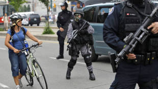 A woman avoids police in riot gear as she takes part in a