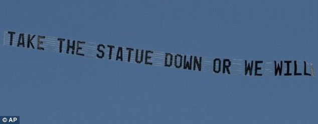 Demands: The banner referred to a monument to Paterno, who coached the team for nearly 50 years before he was fired in disgrace last year