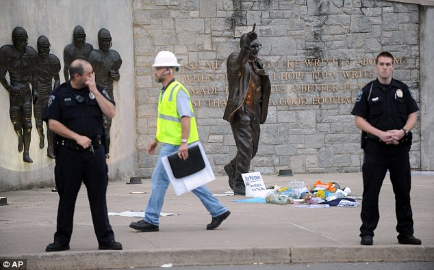 Coming down: Police and construction workers have surrounded the Joe Paterno statue in State College, Pennsylvania as Penn State prepares to remove it