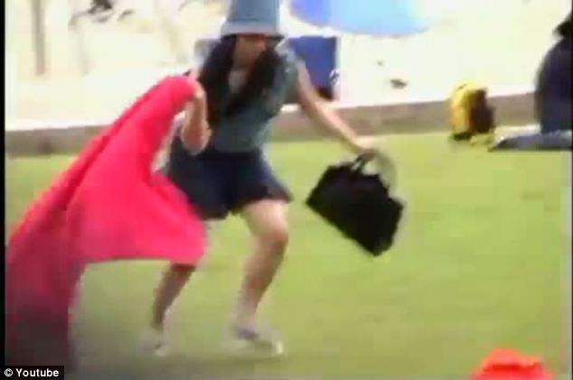 Dash for safety: A young woman grabs her purse and her red blanket to hide from the roaming birds