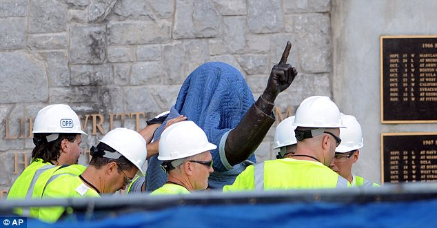 Farewell: Workers are seen carting away the covered statue of ex-Penn State football coach Joe Paterno on Sunday morning