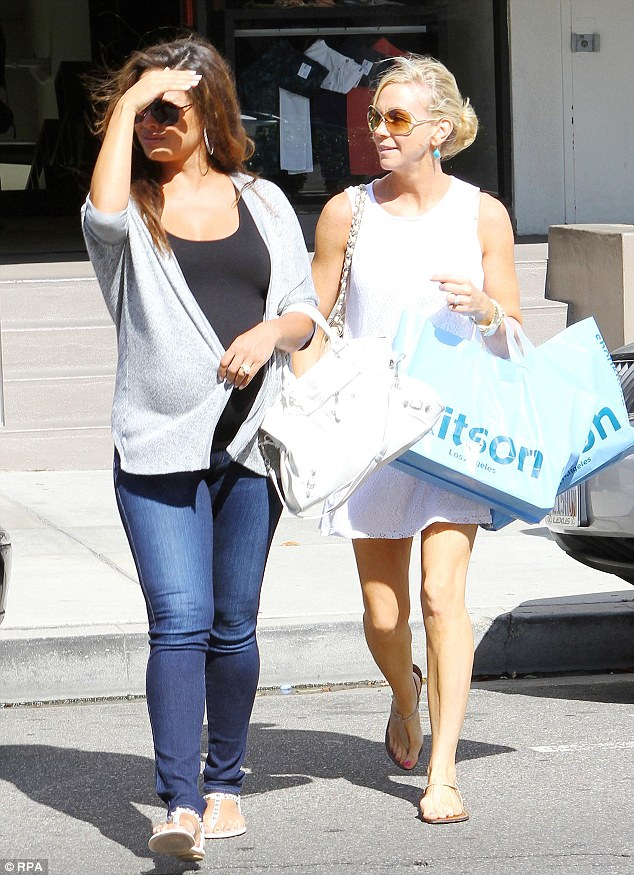 Suddenly shy: Vanessa coyly pulled her grey sweater over her bump when exciting a store with her friend