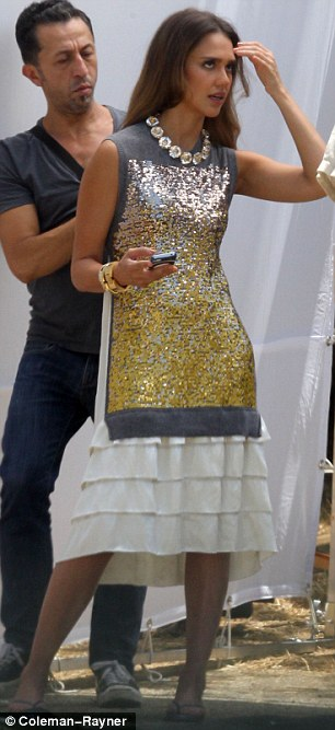 Ready to smoulder: Alba modelled a structured white pleated number, complete with a sequinned gold and silver panel, before slipping into a white jumper dress