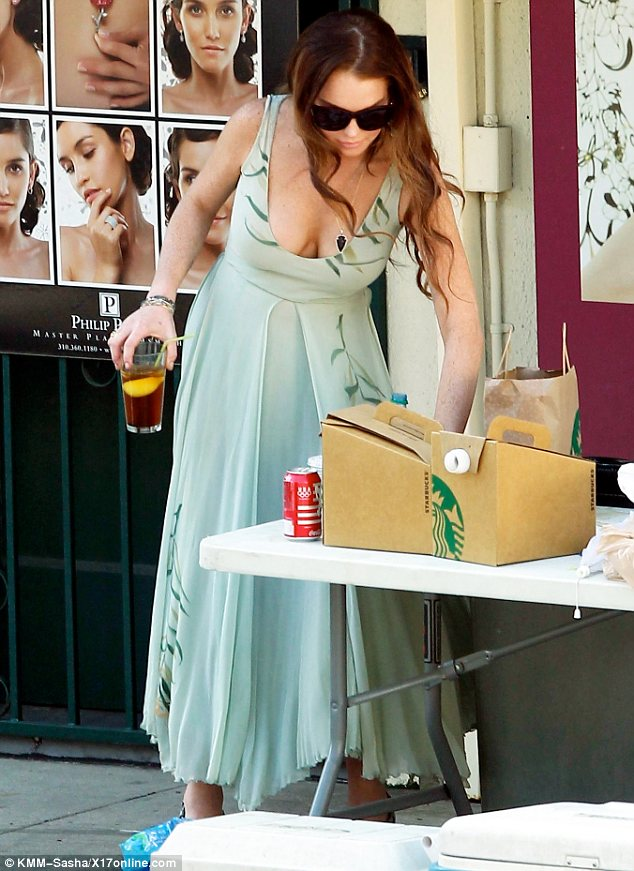 Taking a break: Lindsay checked out the lunch on offer and sipped on an iced tea in between takes