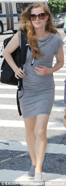 Neutral palette: The star teamed her form-fitting dress with matching tennis shoes as she hurried about New York